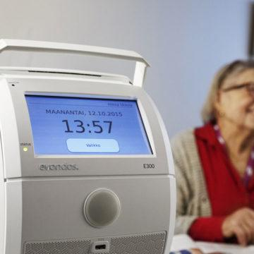 A health technology device with a smiling old woman in the background.