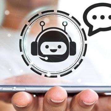 A chatbot icon hovering over a smart phone held by a person.