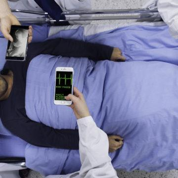 Man lying on a hospital bed while doctors perform diagnoses on their smart phones.
