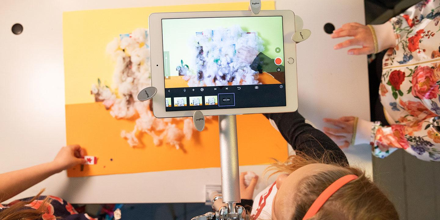 Children filming a crafts video on a tablet computer.