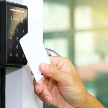 A person opens a digital lock with a key card.