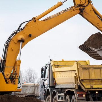 An excavator lifting dirt into a truck.